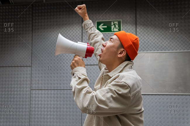 Side view of overwhelmed male protesting in casual clothes screaming in loudspeaker while standing against gray wall in dark room