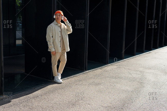 Full length unemotional Asian male in casual outfit enjoying good music via wireless headphones while standing near modern building wall on sunny day