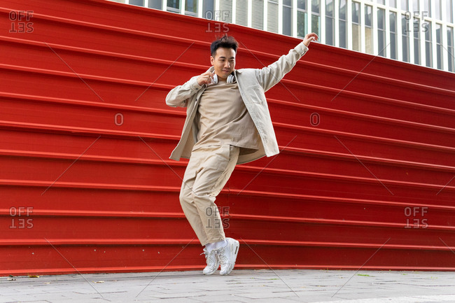 Full body joyful Asian male in casual wear listening to favorite song in wireless headphones while dancing along red metal fence