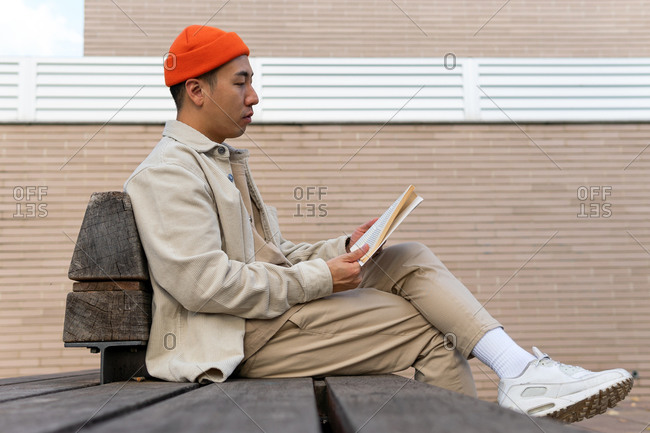 Side view focused Asian male wearing casual clothes reading fascinating book while sitting on wooden bench on street