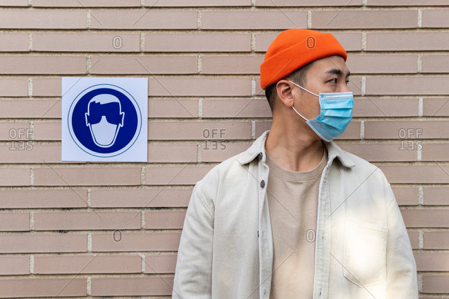 Serious Asian male wearing mask standing near sign building wall illustrating person in protective mask looking away