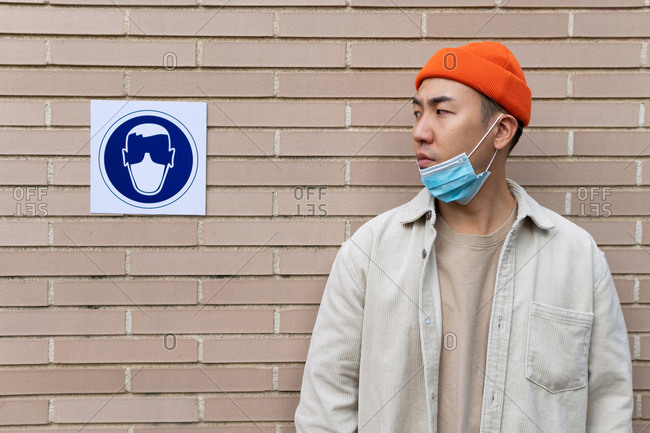 Serious Asian male wearing lowered mask looking at sign near building wall illustrating person in protective mask