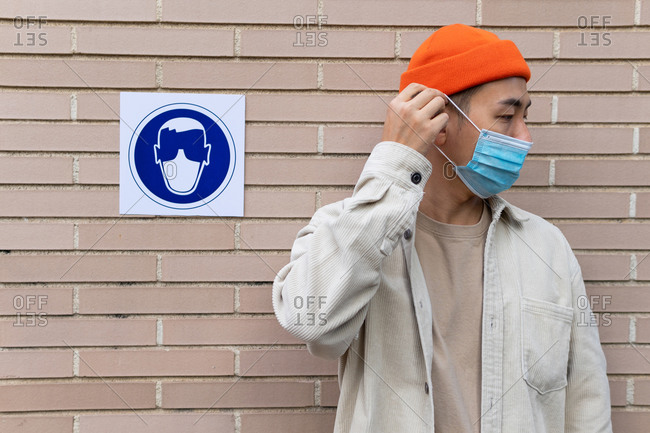 Serious Asian male braking rule by taking off mask standing near sign in building wall illustrating person in protective mask