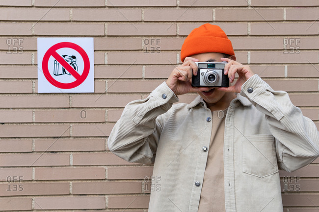 Carefree male taking photos on camera while standing against wall with restriction sign prohibiting photography