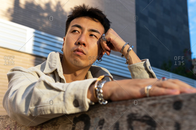 From below pensive Asian male in casual wear sitting near street stone fence and leaning head on hand while looking away thoughtfully