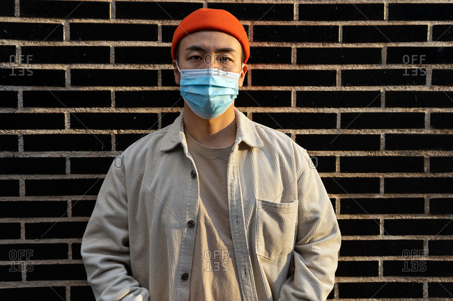 Concentrated Asian male in orange beanie and protective face mask standing calmly on brick wall looking at camera