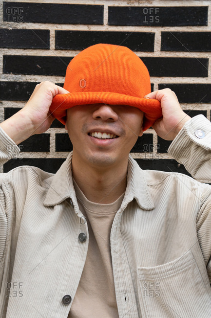 Happy male putting knitted orange hat on head and covering eyes while standing against black brick wall