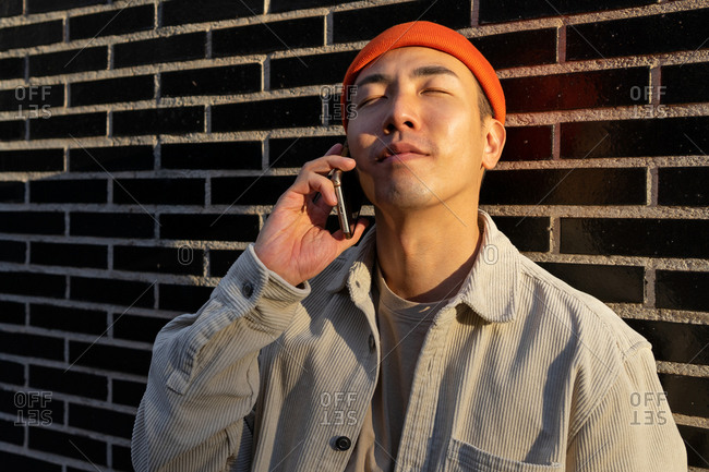 Content Asian male wearing casual outfit having pleasant conversation via mobile phone and standing with eyes closed on brick wall background