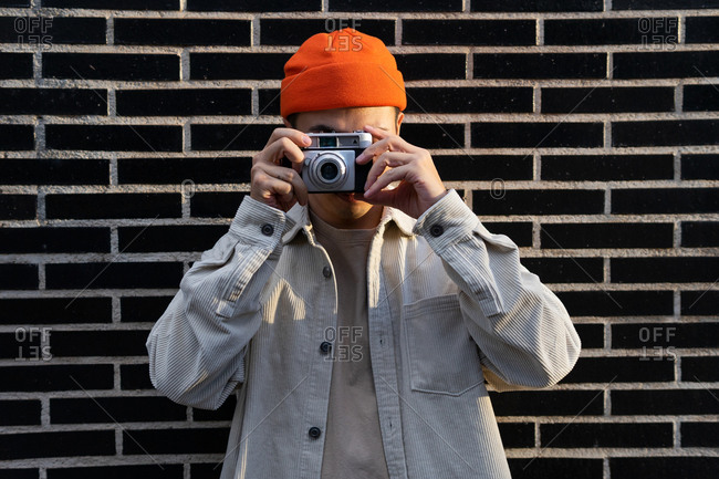 Crop unrecognizable male taking photos on camera while standing against brick wall on the street