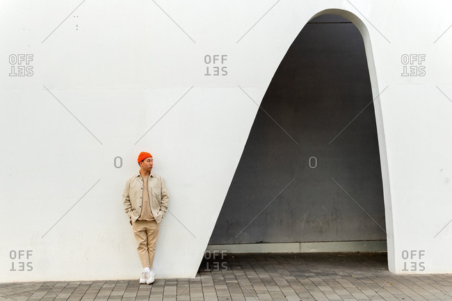 Full length thoughtful Asian male wearing casual clothes and orange hat leaning with hands in pockets on white building wall with creative arch