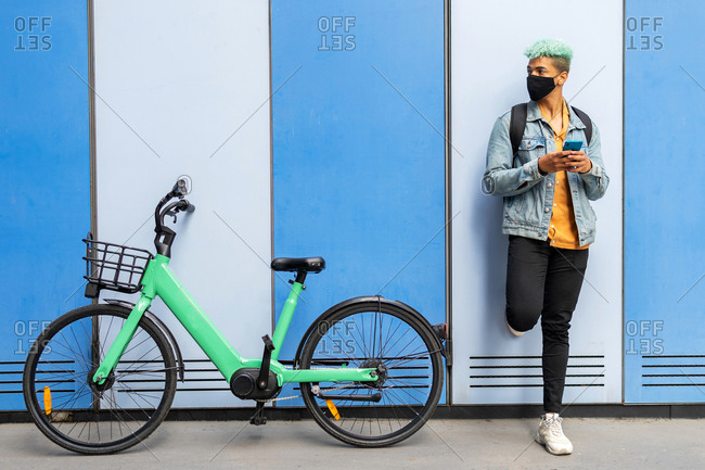 African American male hipster with dyed blue hair and in protective mask standing near wall with bicycle and browsing smartphone in city during coronavirus epidemic