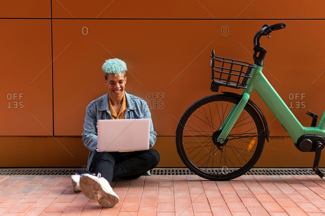 Smiling black male hipster with dyed hair using laptop while working on remote project on the street near modern bike