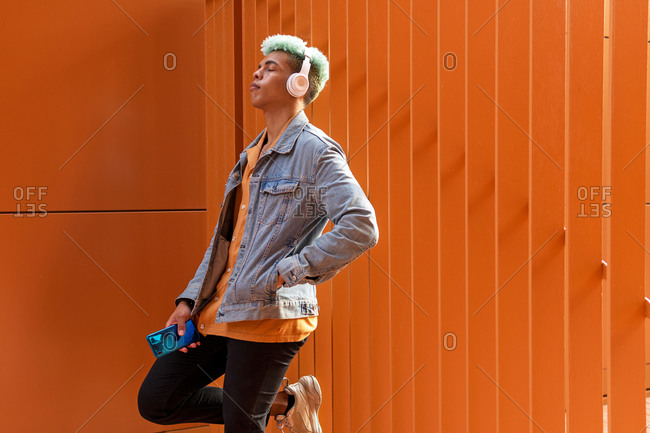 Side view of carefree black male with dyed hair leaning on metal wall and enjoying calm songs in headphones at weekend in city