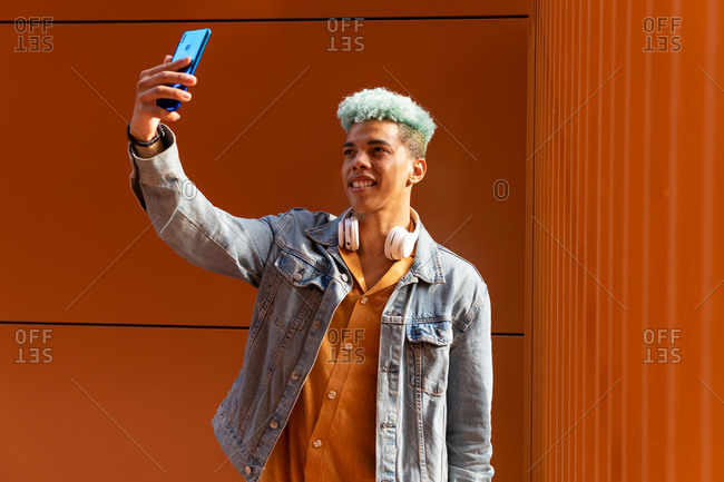 Cheerful African American young male hipster with dyed blue hair using smartphone and taking self portrait in city against vibrant orange wall
