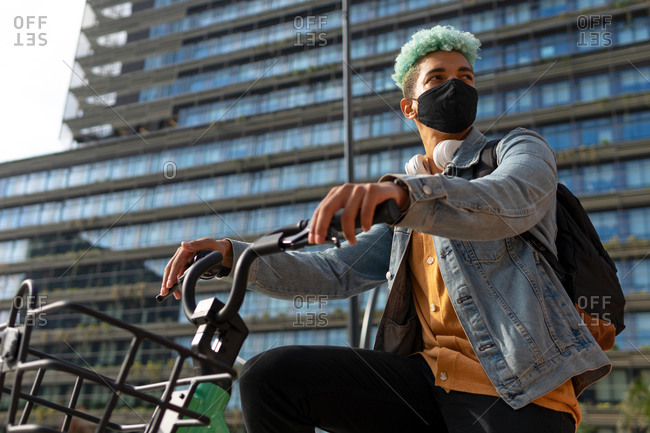 Low angle of black male hipster in protective mask riding modern bike in city during coronavirus outbreak and looking away