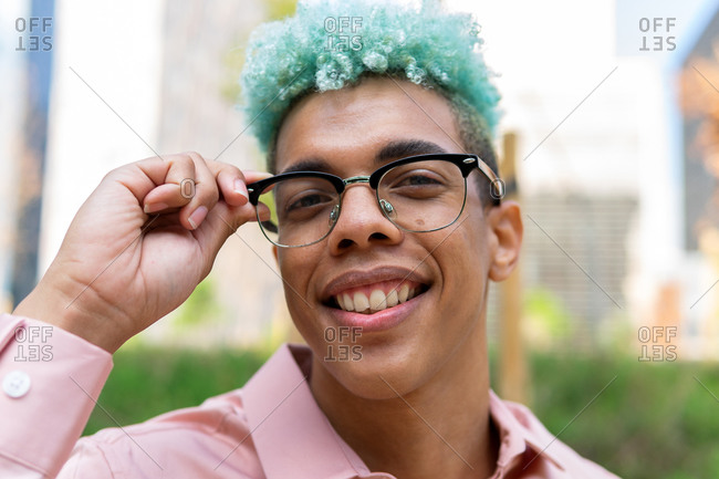 Delighted African American male with dyed blue hair and in stylish eyeglasses standing on street and cheerfully looking at camera