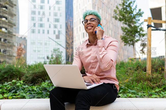 Glad African American businessman with blue hair sitting on street with laptop and talking about project on smartphone during distant work in city