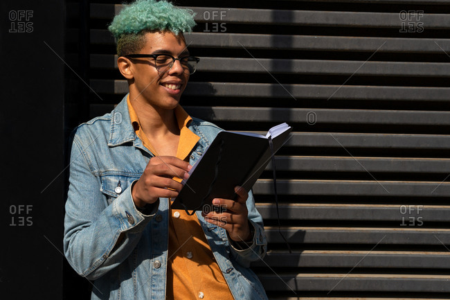 Smiling black male hipster standing on street and enjoying interesting story in book while entertaining at weekend in city