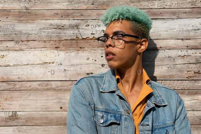 Optimistic black male hipster with blue curly hair standing near wooden building background on sunny day while looking away