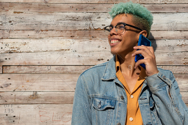 Optimistic black male hipster with blue curly hair standing near wooden building and speaking on smartphone on sunny day while looking away