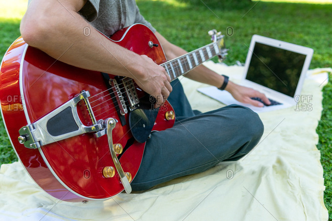 Unrecognizable male musician sitting on blanket with laptop and choosing tutorial while preparing for playing modern electric guitar in park