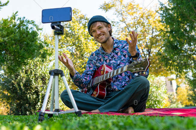 Ground level of handsome man sitting with electric guitar in park and recording video on smartphone for blog on social media