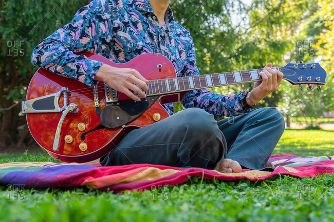 Cropped unrecognizable male musician sitting on lawn and playing electric guitar on sunny day in park
