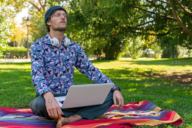 Calm male entrepreneur sitting in park with laptop and doing yoga in Lotus pose with closed eyes while having break during remote work