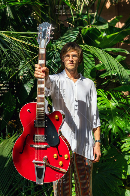 Confident male musician in hippie outfit standing in exotic garden with modern electric guitar and looking at camera