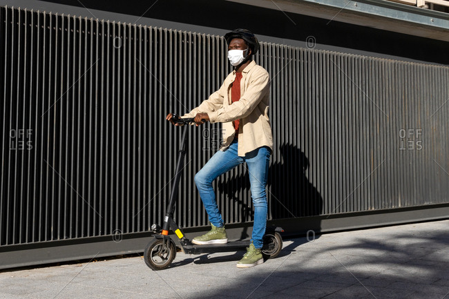 Side view of African American male in medical mask and helmet riding modern electric scooter along sunny street in city during coronavirus pandemic
