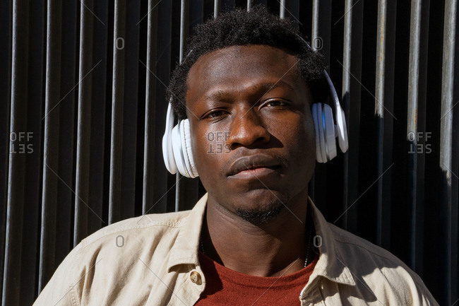 Tranquil African American male listening to music in wireless headphones while leaning on metal wall in street and looking at camera