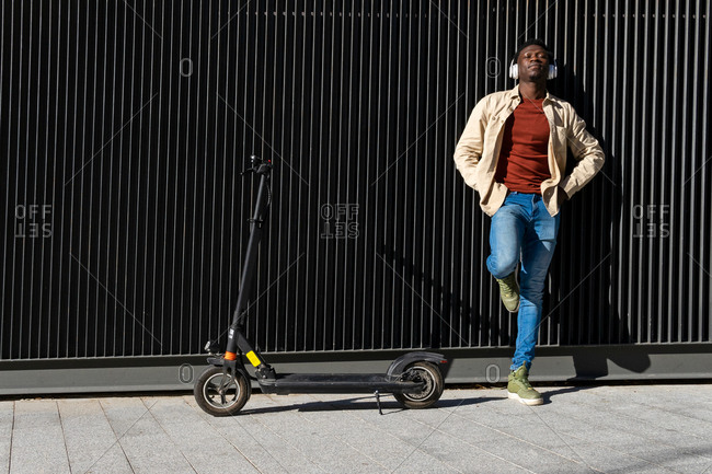 Happy African American male in helmet standing with modern electric scooter along sunny street in city