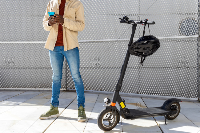 Unrecognizable African American male in casual style outfit standing on street near electric scooter and surfing Internet on cellphone on sunny day