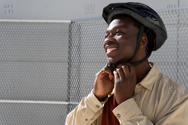 Delighted African American male putting on protective helmet while standing on the street in the city and getting ready for ride