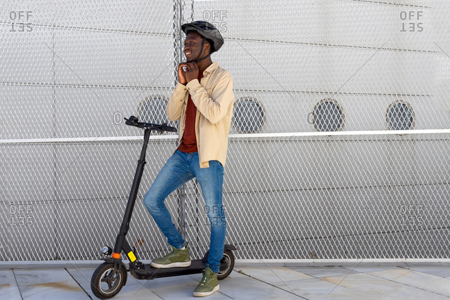 Delighted African American male putting on protective helmet while standing on electric scooter in city and getting ready for ride