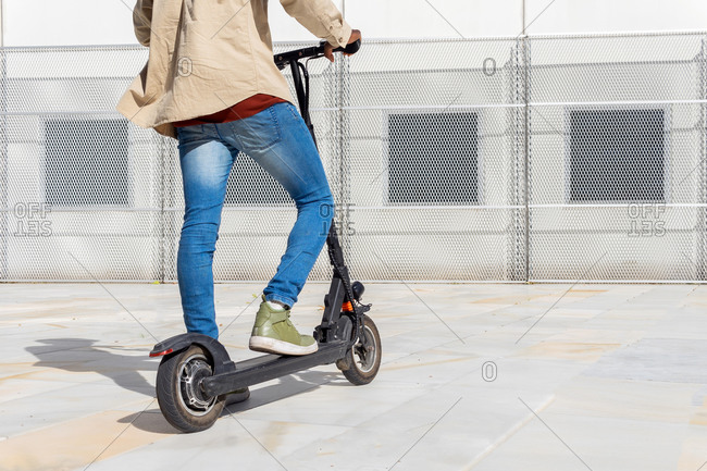 Back view of faceless ethnic male standing on modern electric scooter near metal wall on sunny day in city