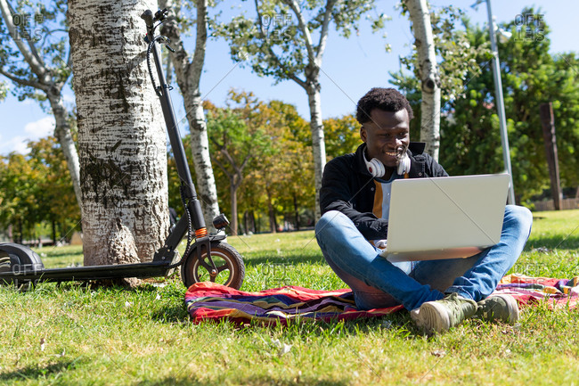 Happy ethnic male lying on blanket working on laptop and scooter near tree in urban garden while enjoying summer day and looking away