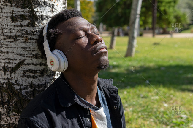 Dreamy African American male in wireless headphones leaning on tree trunk in garden and enjoying calm songs with closed eyes