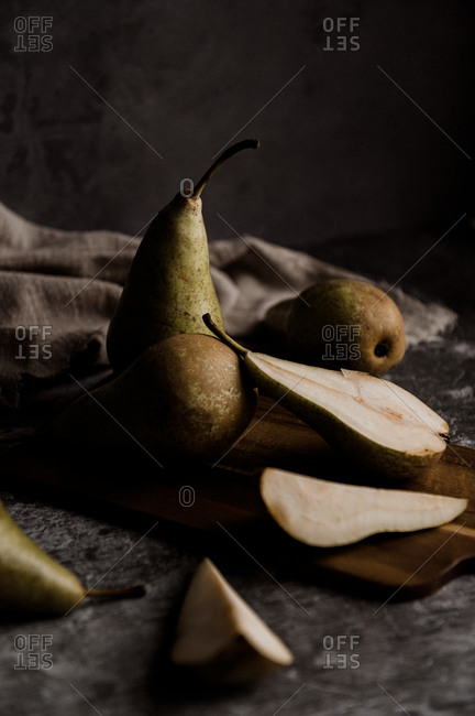 Whole and cut fresh ripe green pears arranged on table in dark studio