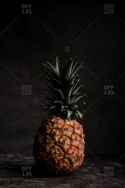 Whole ripe tropical pineapple with verdant foliage on table against black background in dark studio