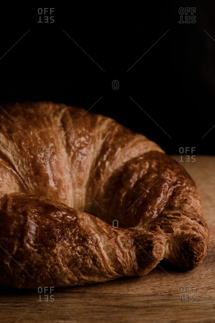 Closeup of appetizing crispy croissant placed on wooden table against black background