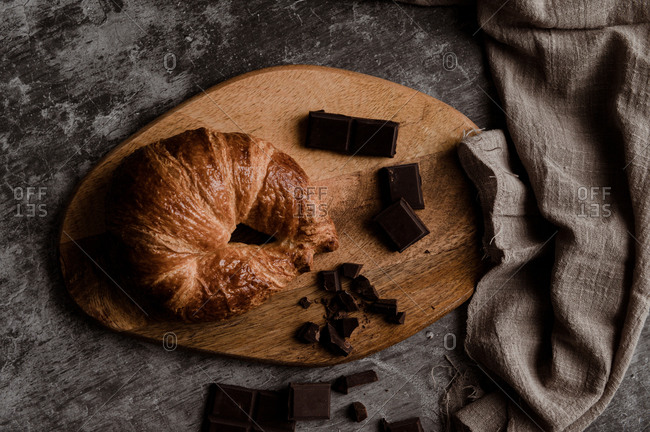From above of delicious fresh crusty croissant and pieces of dark chocolate composed on wooden board on shabby table with linen fabric