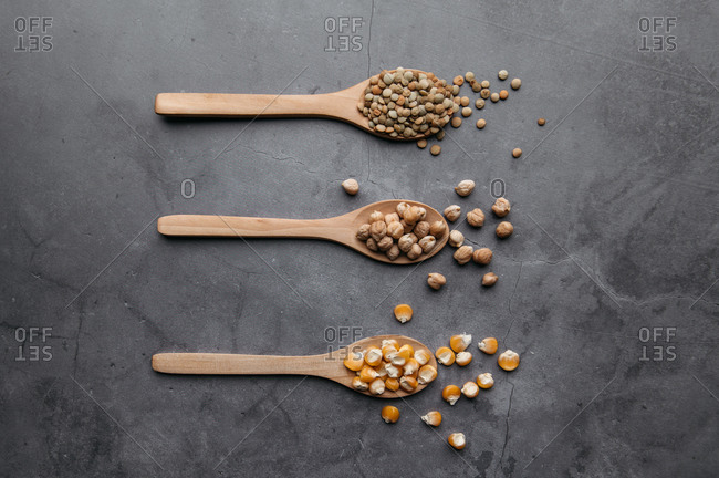 Top view of assorted dried ingredients placed in wooden spoons and scattered on black table in kitchen
