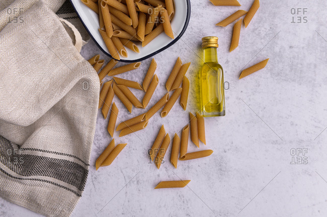 From above of dried Penne pasta in metal bowl and bottle of virgin olive oil arranged on table with napkin in kitchen