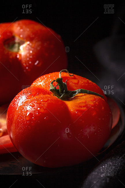 Fresh ripe red grape tomatoes with water drops in metal bowl placed on table dark background