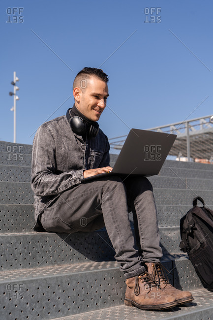 Cheerful male freelancer in headphones sitting on stairs and typing on laptop while working outside