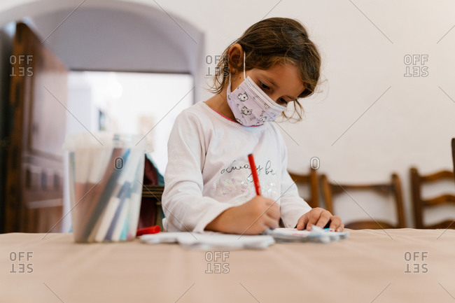 Concentrated little child in mask sitting at wooden table at home and drawing with markers while entertaining during coronavirus quarantine