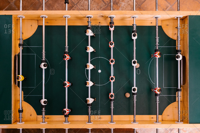 Top view of retro table soccer with metal bars and plastic figurines of players in bright room