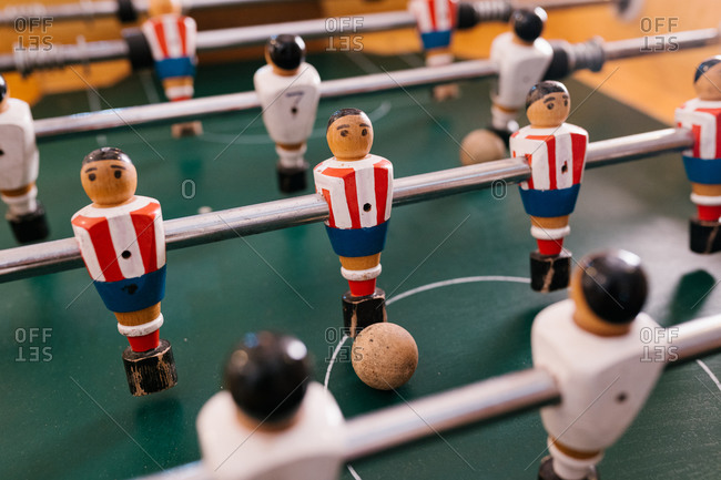Retro table soccer with metal bars and plastic figurines of players in bright room
