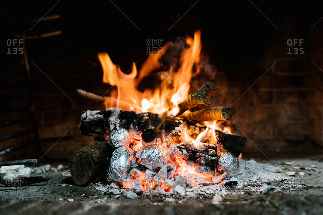 Potatoes in aluminum foil baked in burning flame of fire in cozy chimney in rustic house